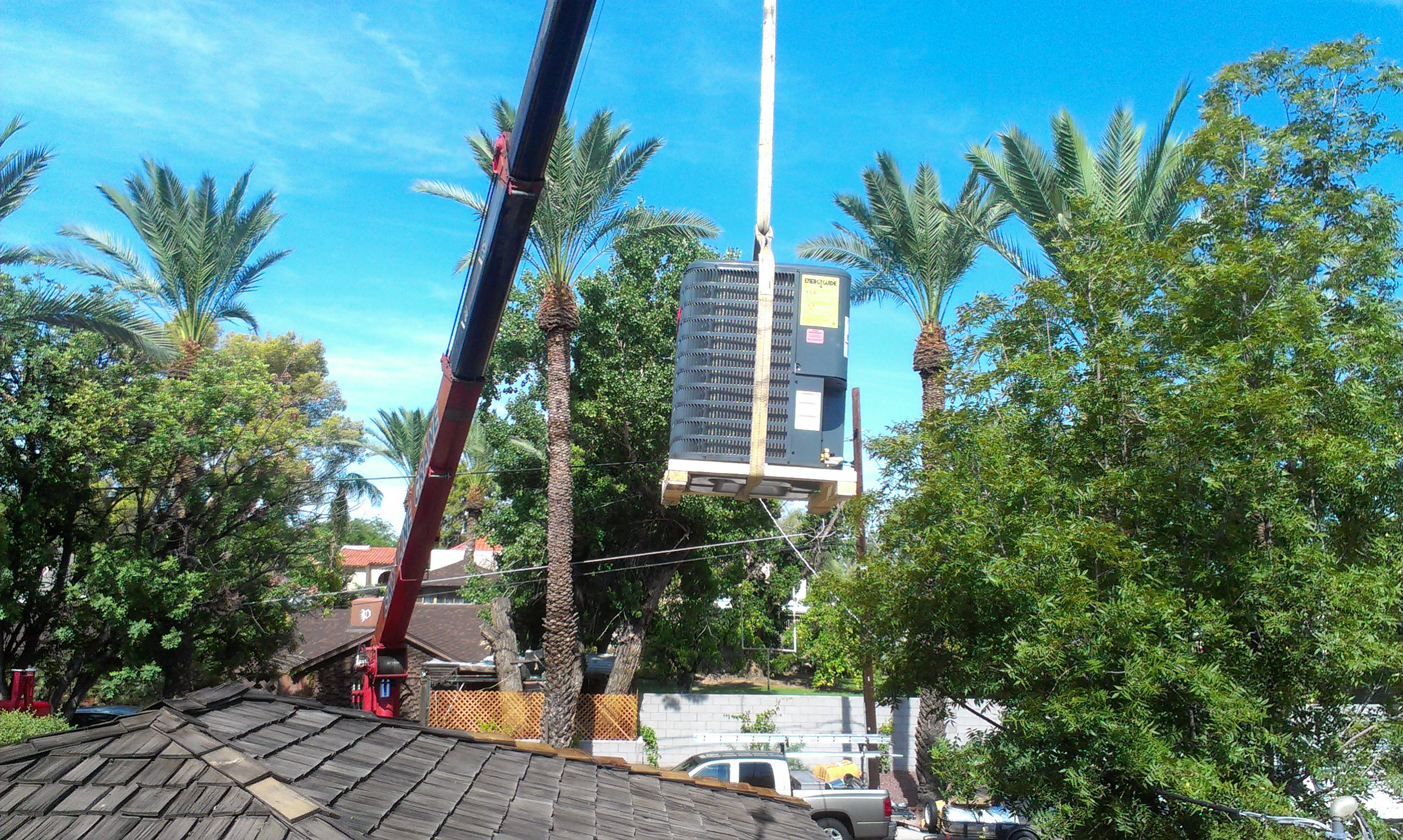 Goodman condenser being hoisted to roof by crane