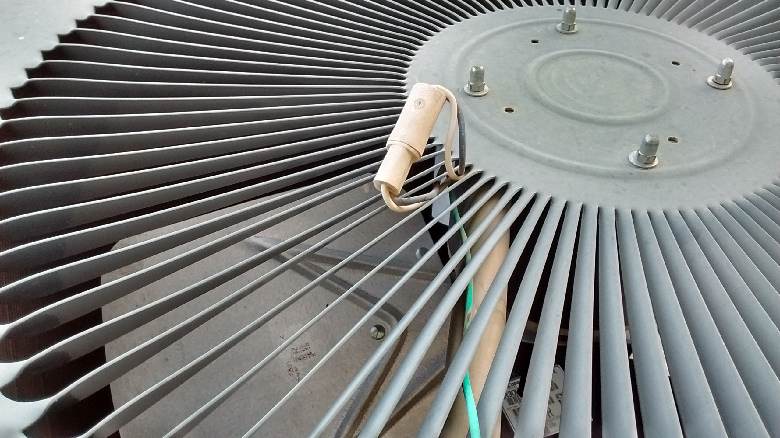 air conditioner with wires and plug from the fan motor sticking out from the top of the unit